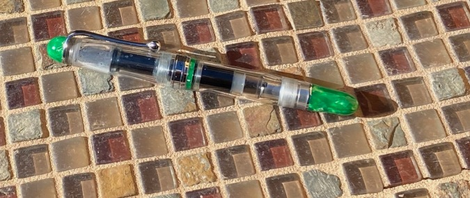 Aurora 88 Minerali clear barrel, cap, green endcaps and ring band.